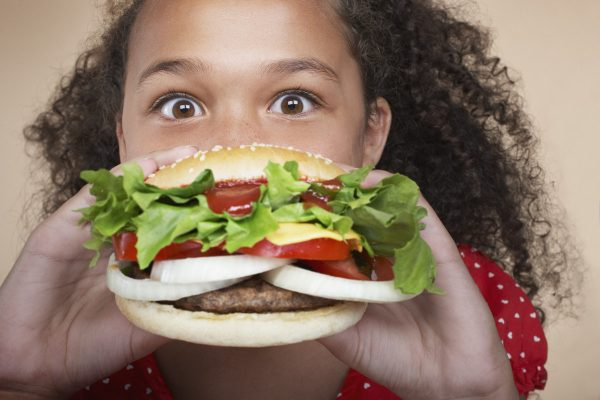 Little girl enjoying a homemade hamburger